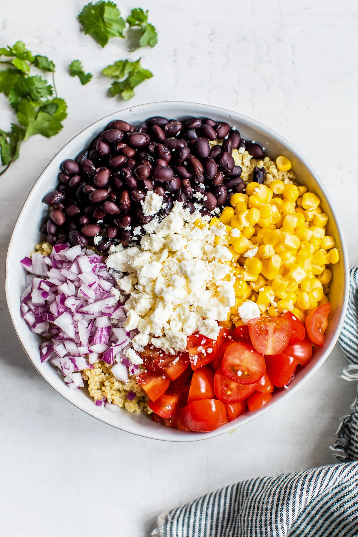 Ingredients for Mexican Quinoa Salad in a bowl before being mixed together.