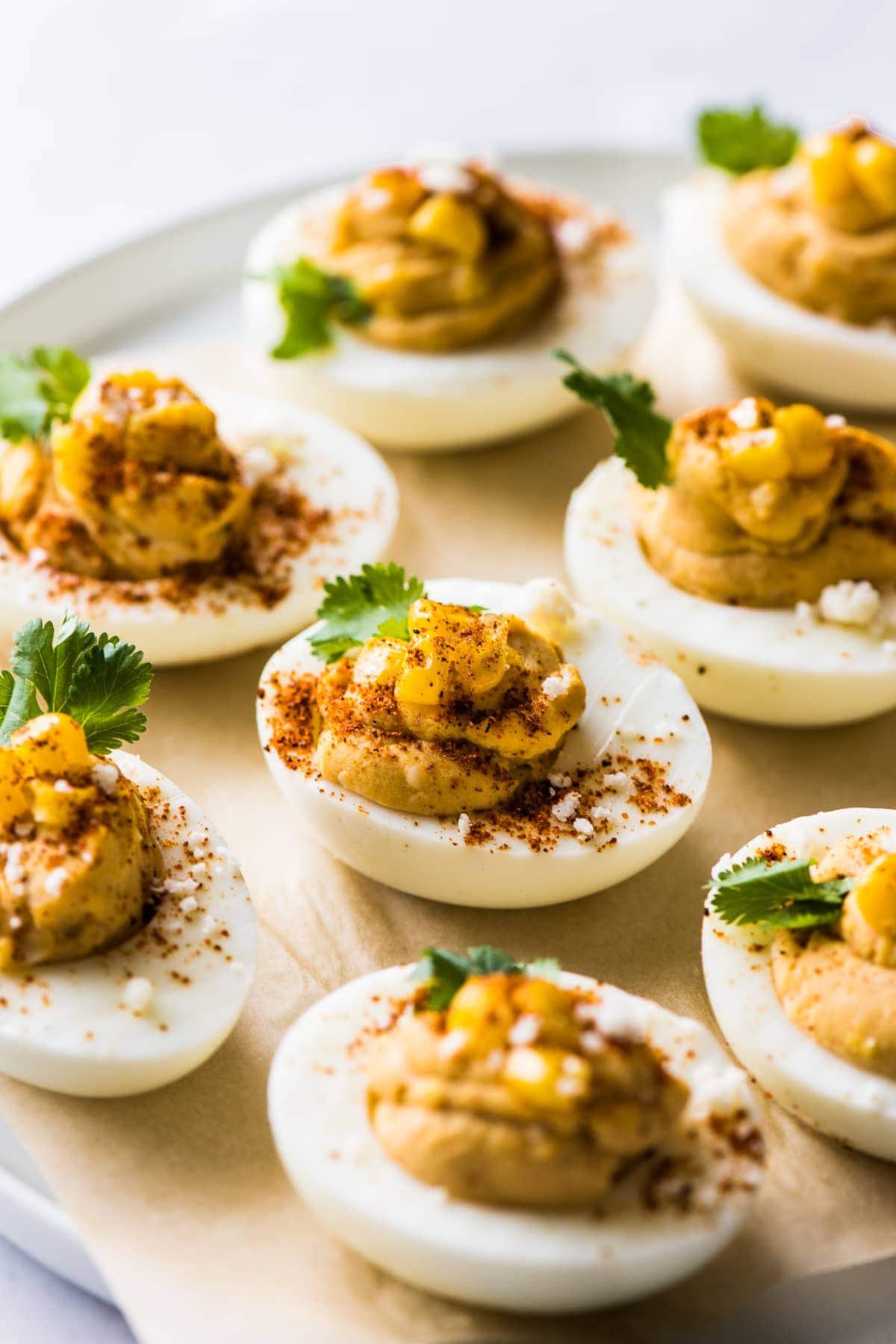 Mexican deviled eggs on a plate topped with corn, cilantro, chili powder, and cotija cheese.