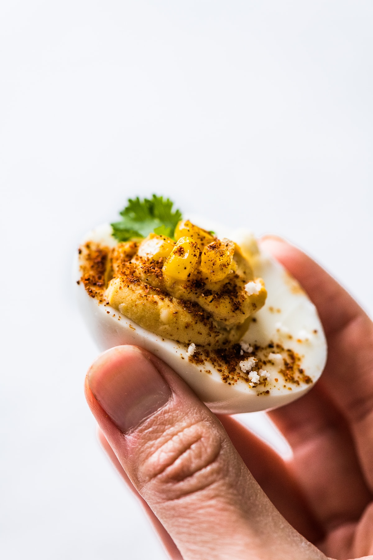 A hand holding a Mexican street corn deviled egg.