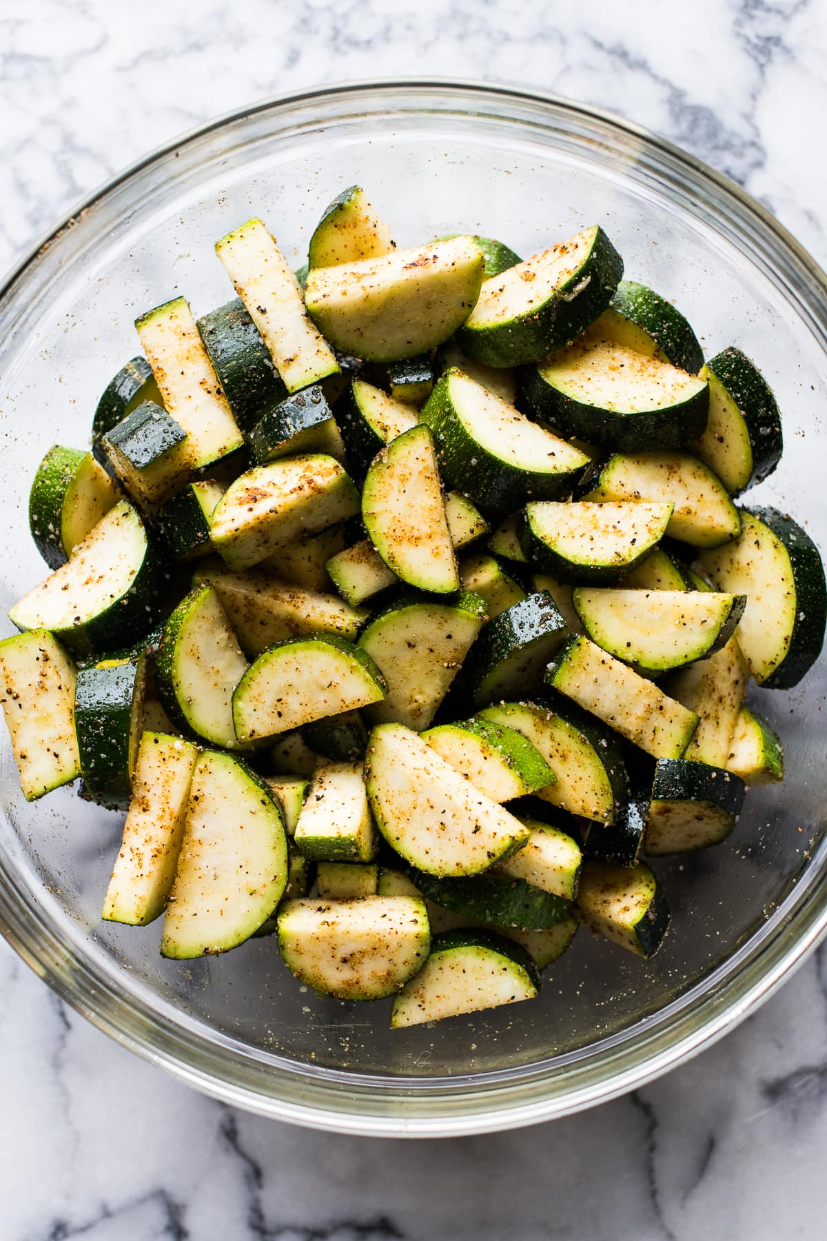 Sliced zucchini in a bowl tossed with spices.