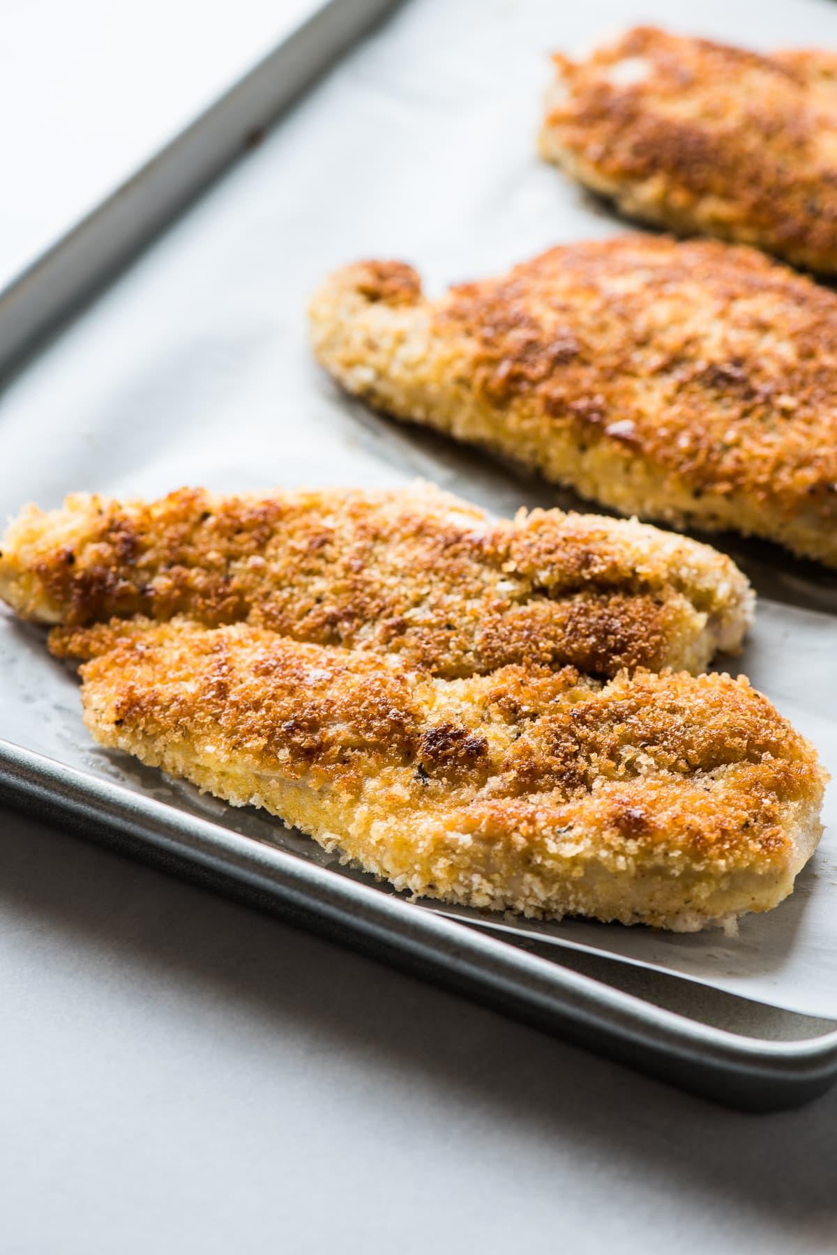 Milanesa de Pollo (Chicken Milanese) cutlets on a baking sheet.