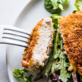A Milanesa de pollo sliced and ready to eat on a fork.
