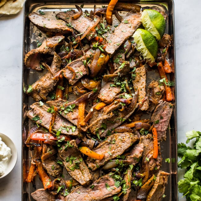 Sheet pan steak fajitas topped with cilantro.