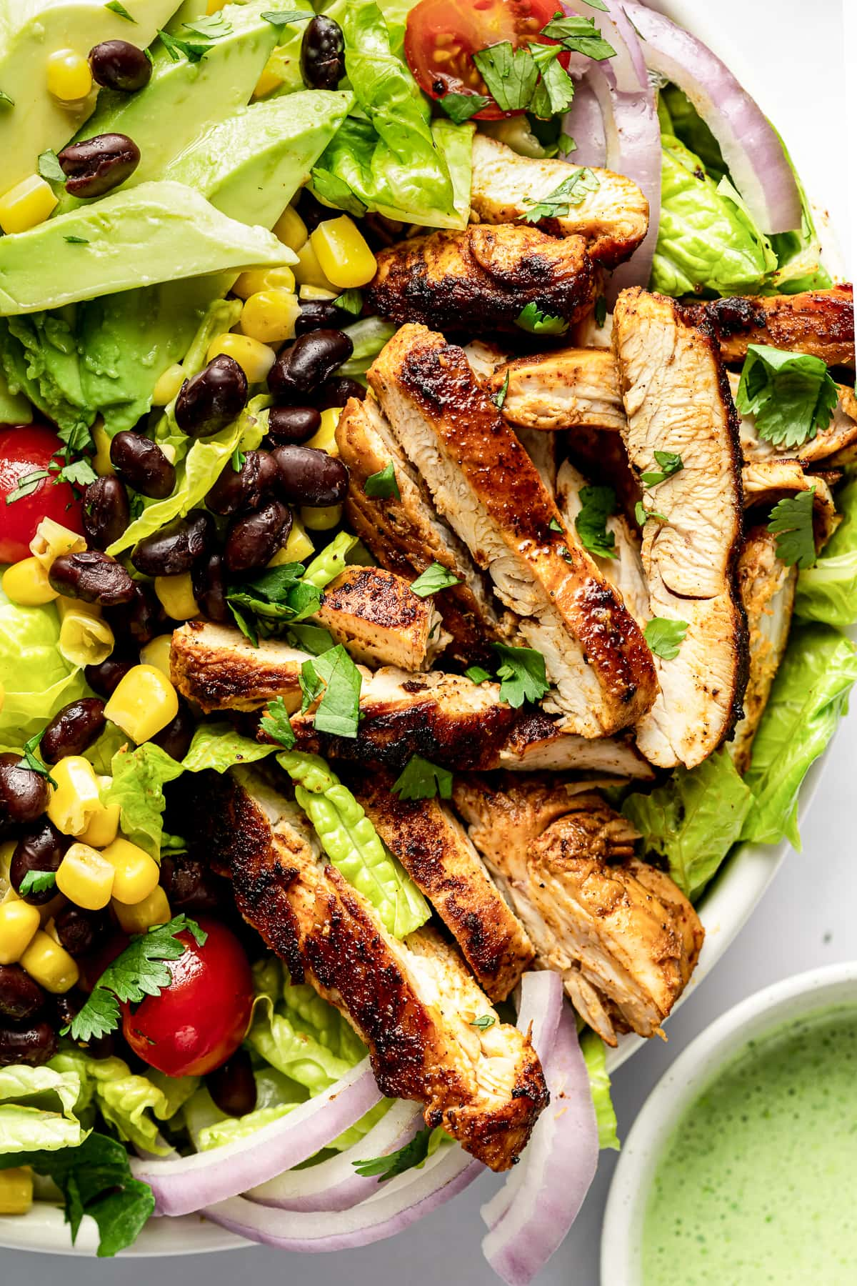 Southwest chicken salad topped with sliced marinated chicken, black beans, corn, and tomatoes.