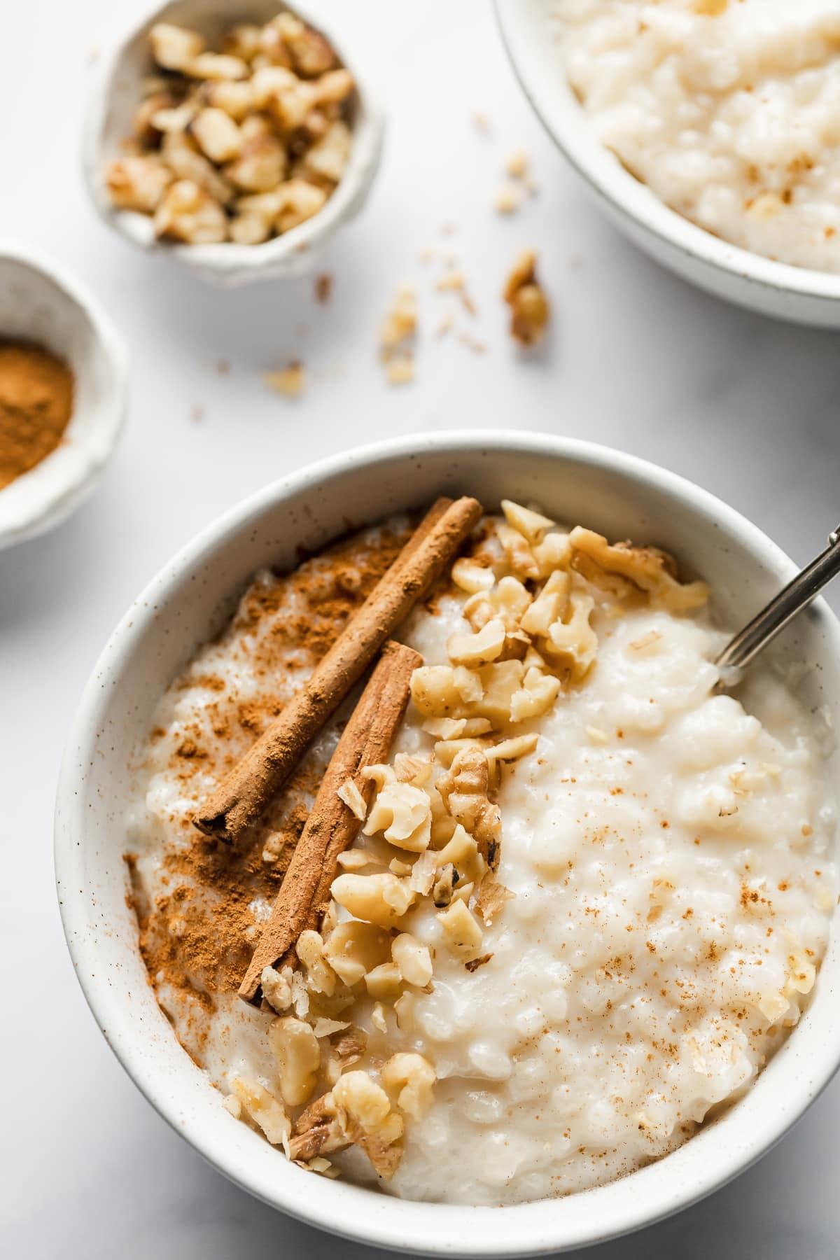 Arroz con leche en un bol cubierto con nueces picadas y canela.