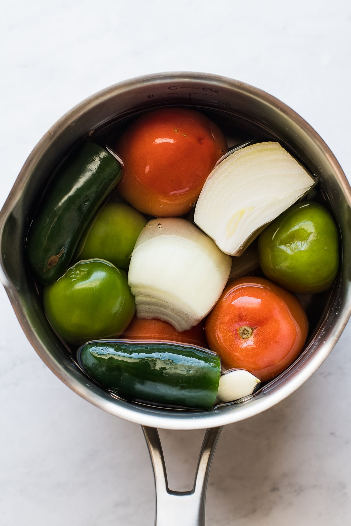 Tomatoes, onions, tomatillos, and jalapenos in a pot.