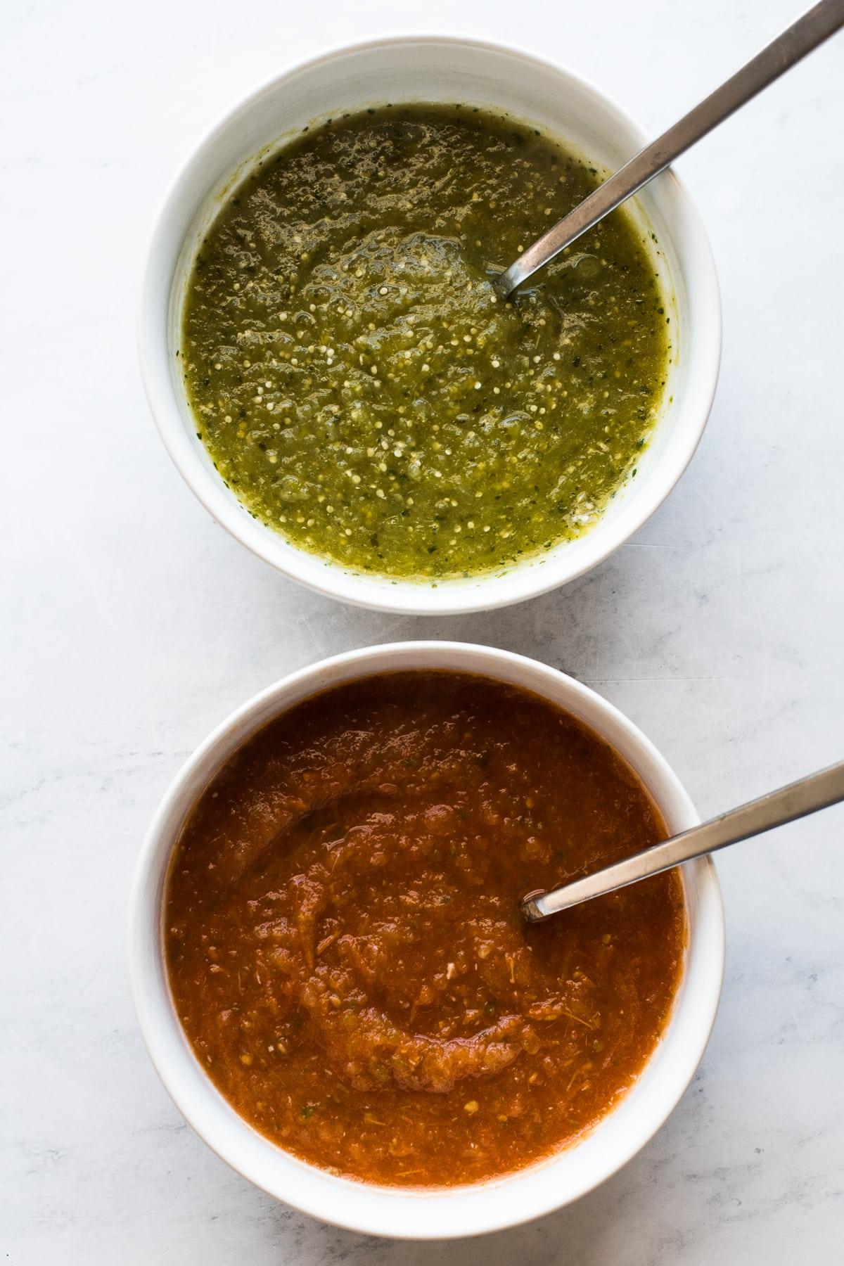 Salsa roja and salsa verde in bowls for huevos divorciados.