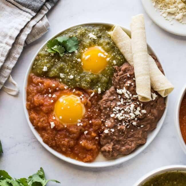 Huevos Divorciados on a plate served with refried beans.