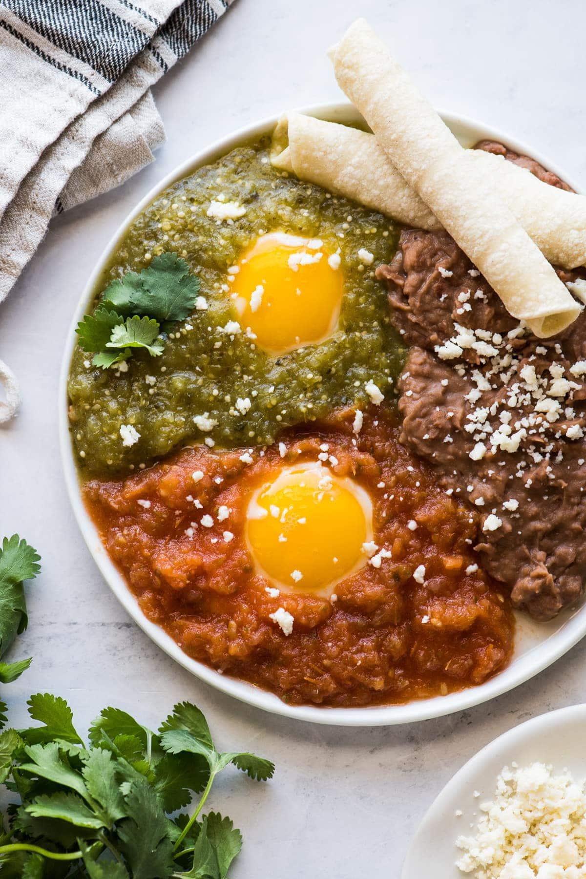 Huevos divorciados on a plate with salsa roja and salsa verde.
