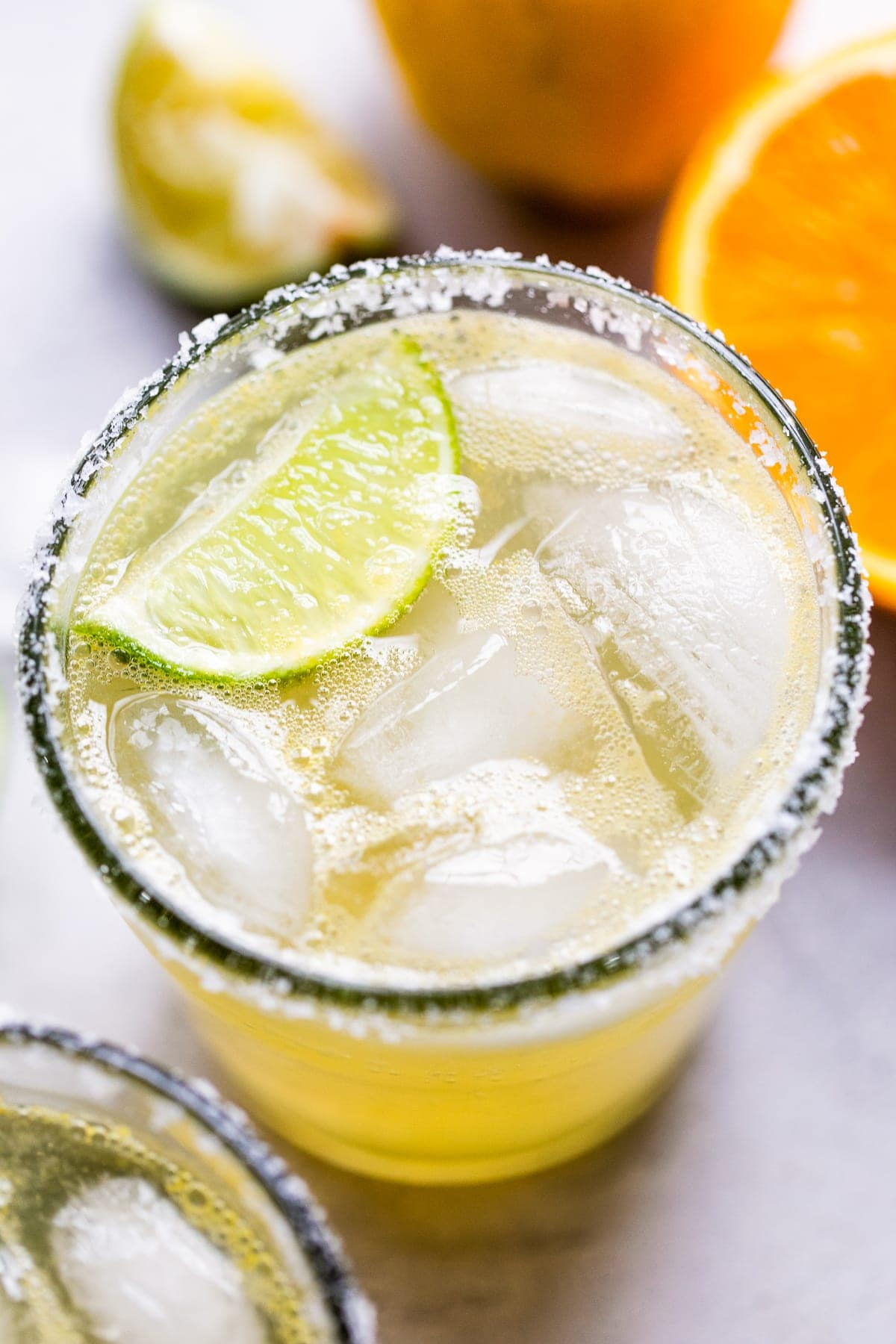 A classic virgin margarita cocktail in a glass with ice and a lime wedge.