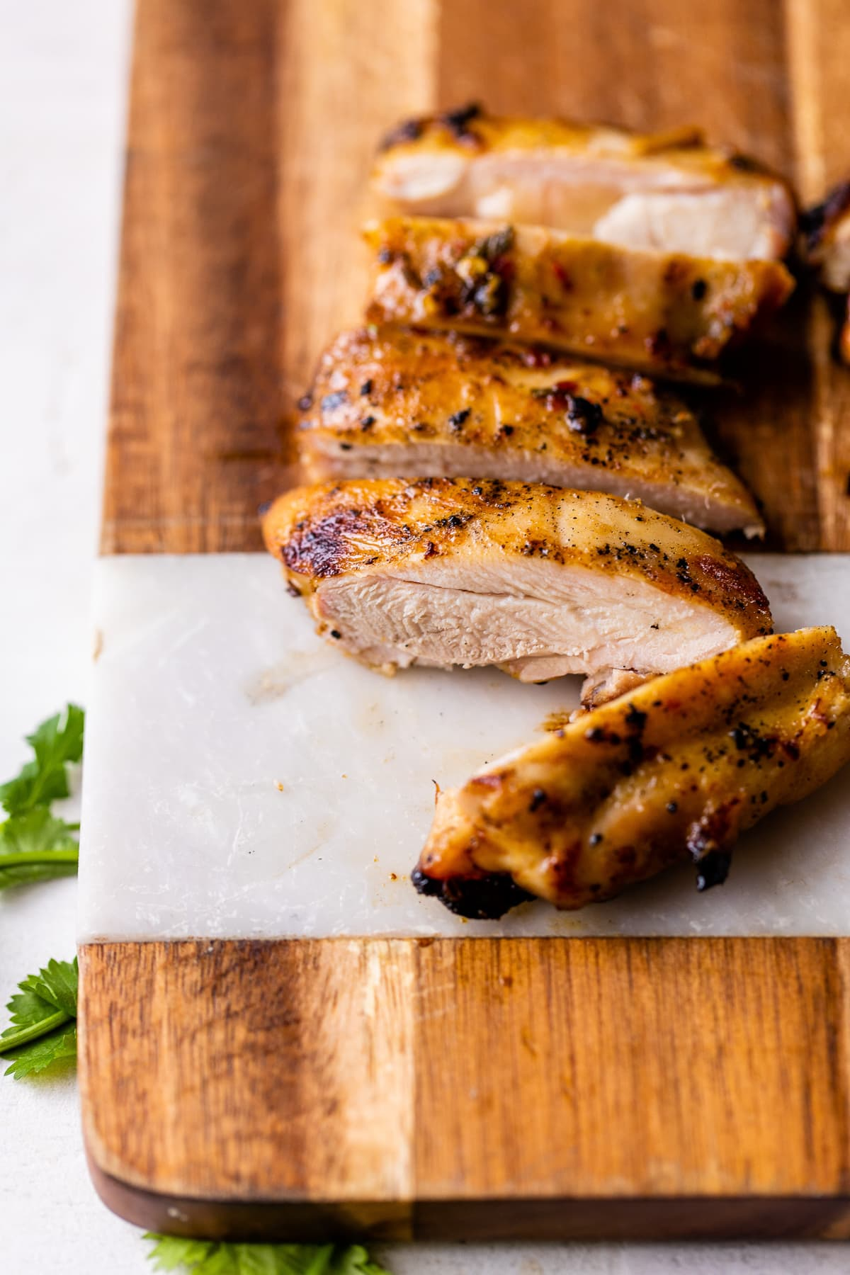 Sliced juicy lime marinated chicken on a cutting board.