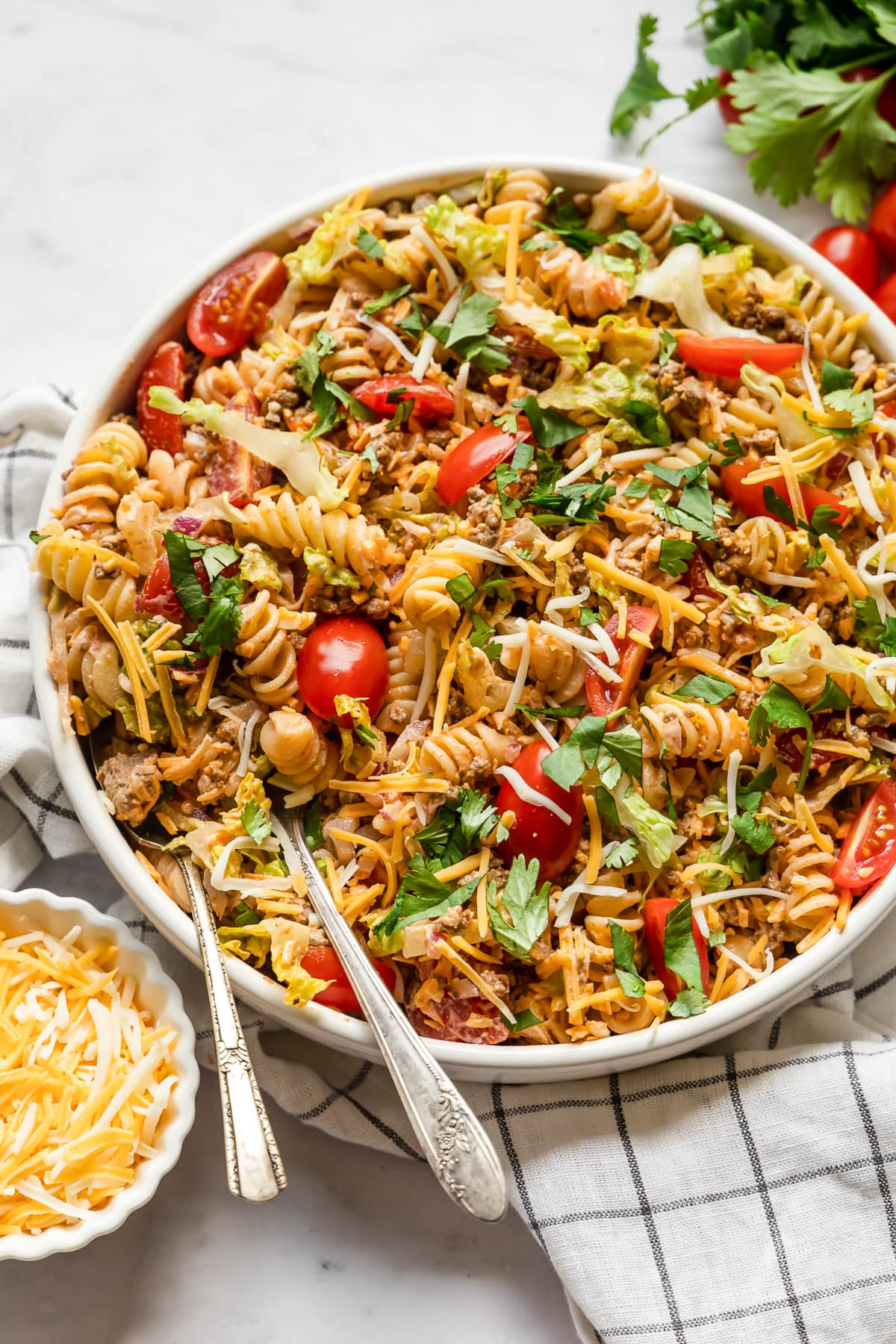 Taco pasta salad topped with shredded cheese and tomatoes.