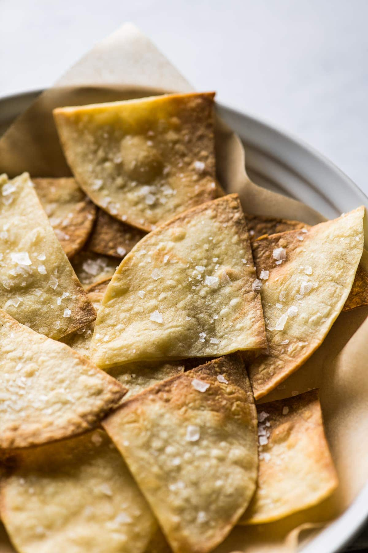 Air fryer tortilla chips seasoned with flaky sea salt.