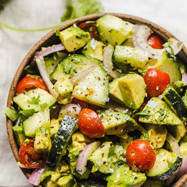 A bowl of avocado salad with cucumbers.