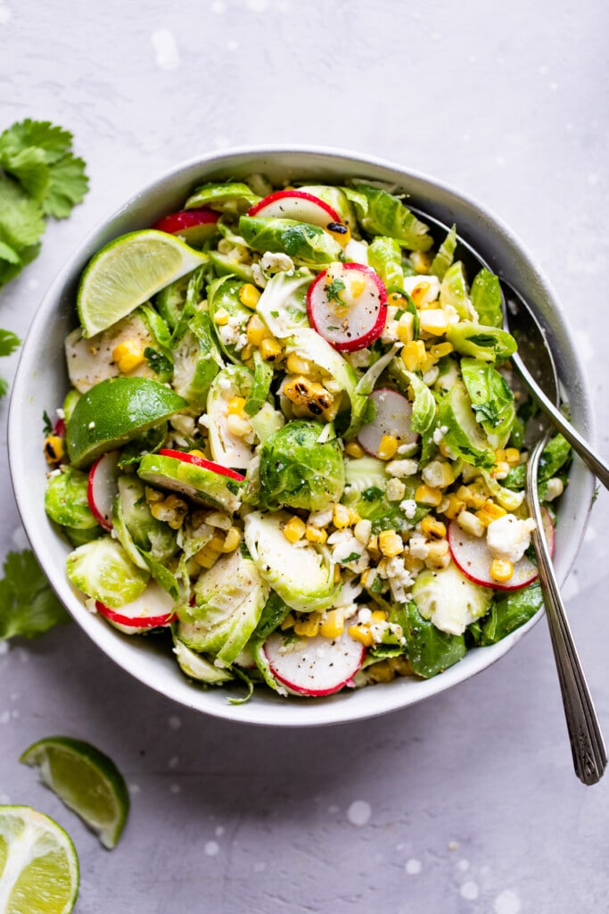 Mexican Brussels Sprout Salad topped with sliced radishes and lime wedges.