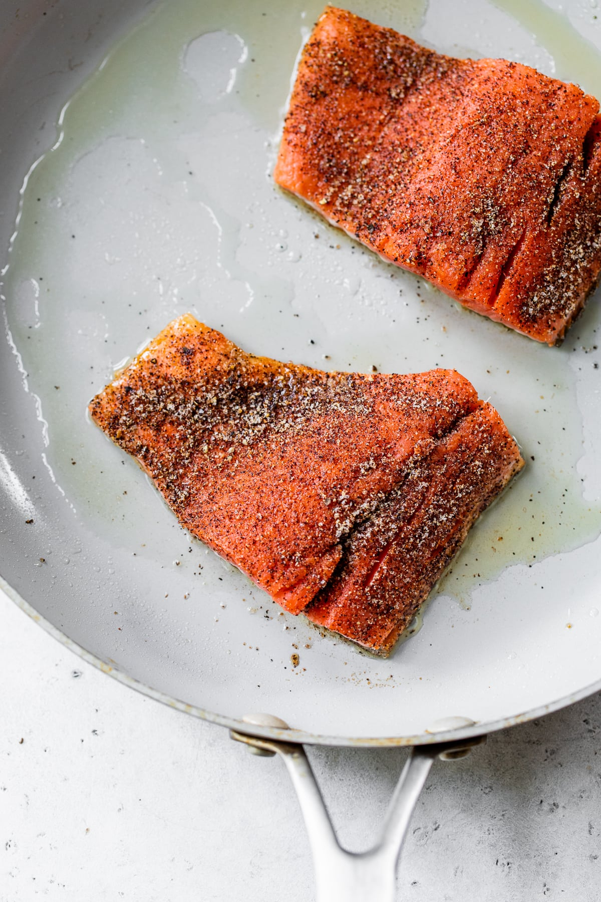 Salmon fillets cooking on a skillet.