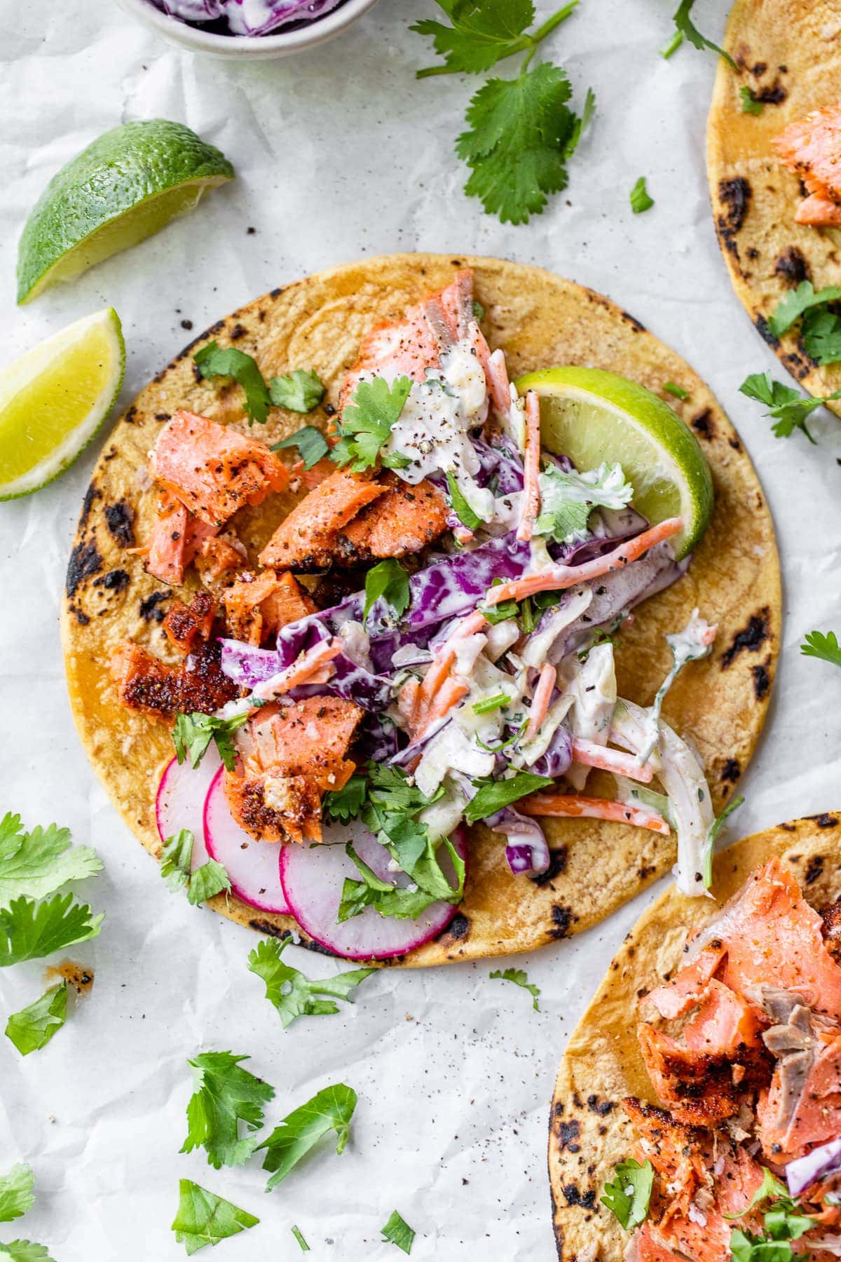 Salmon tacos topped with a creamy slaw and fresh cilantro.