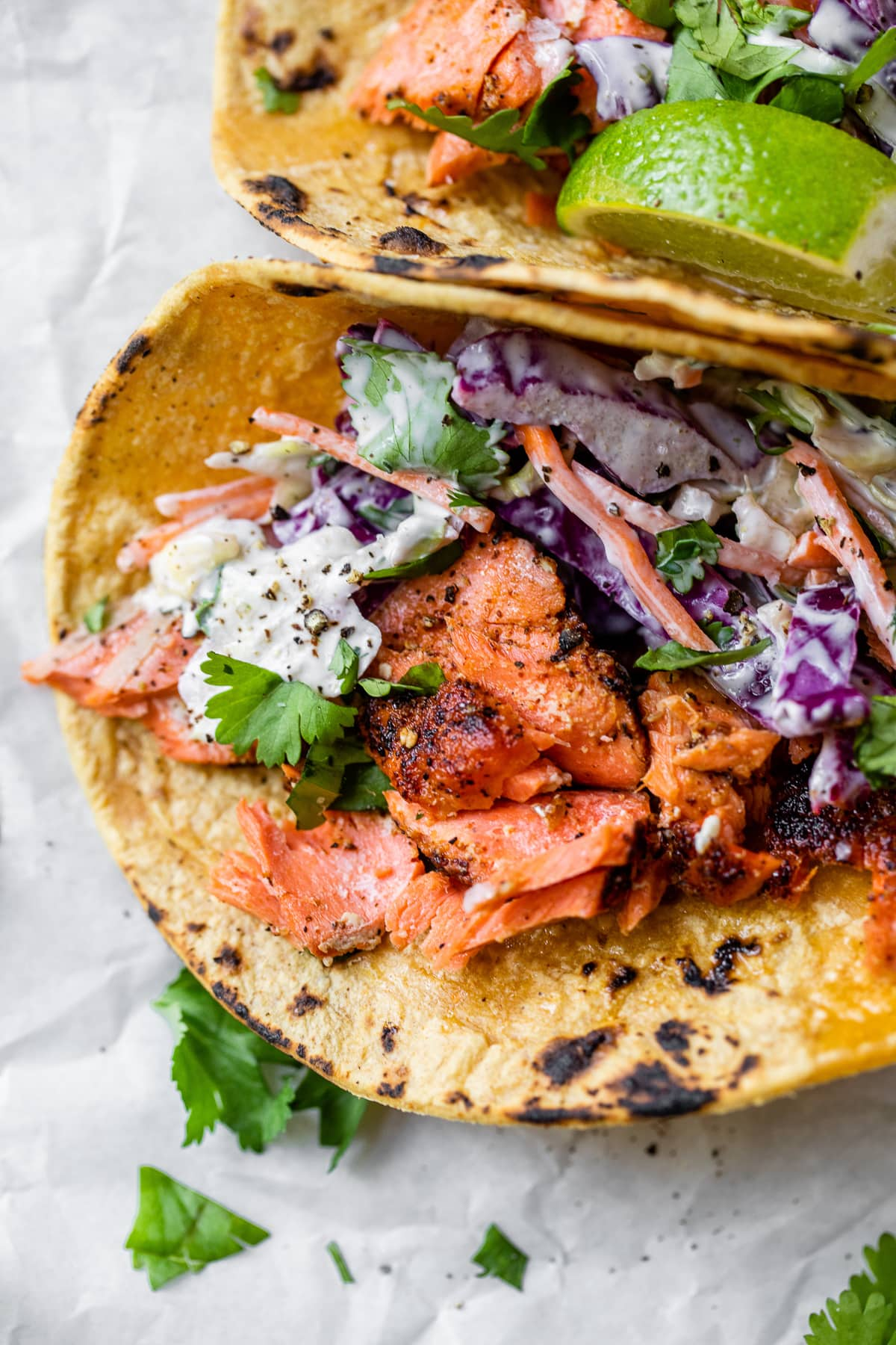 Easy salmon tacos in a corn tortilla topped with fresh cilantro leaves.