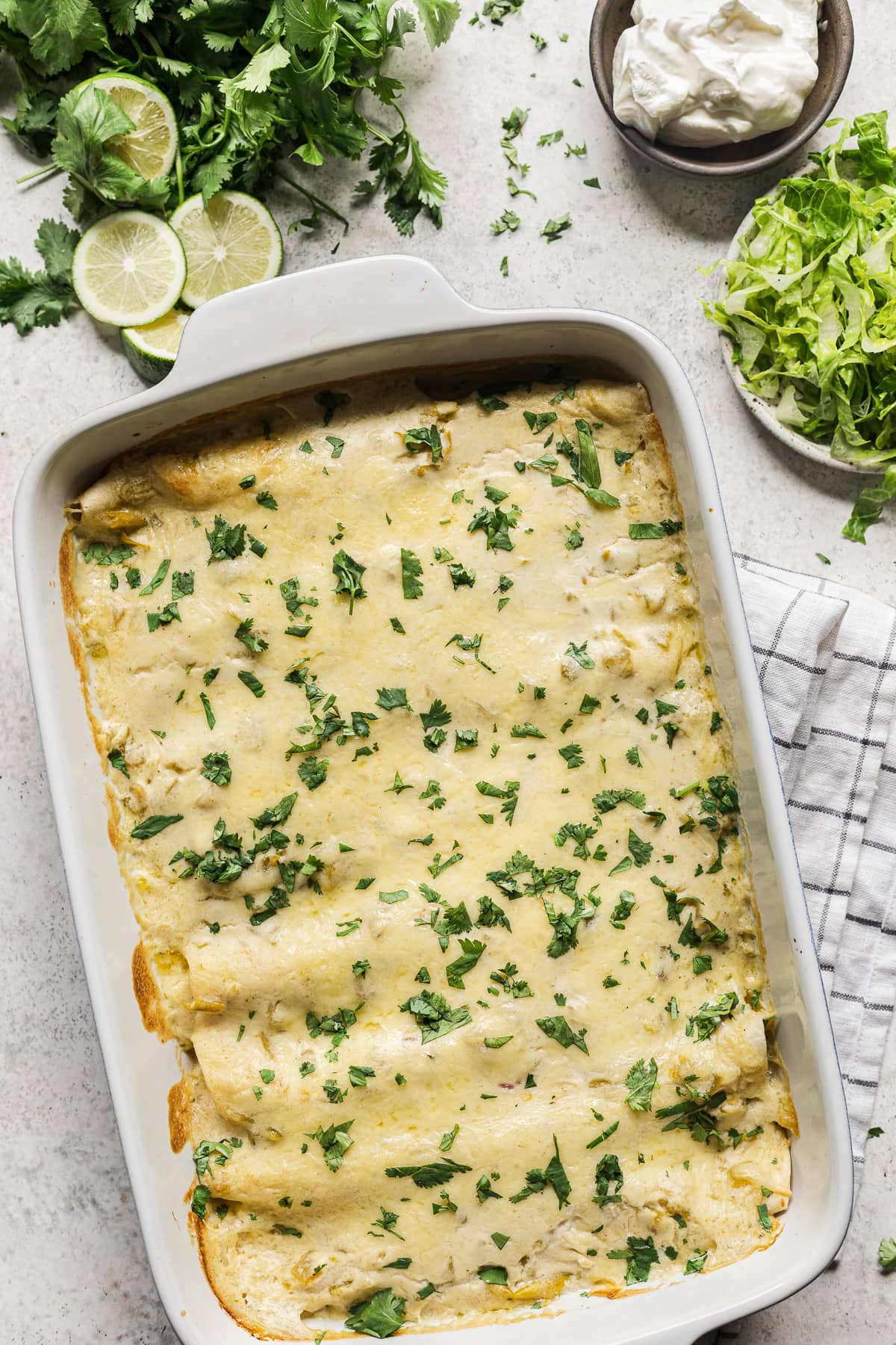 A baking dish full of white chicken enchiladas ready to be served and eaten.