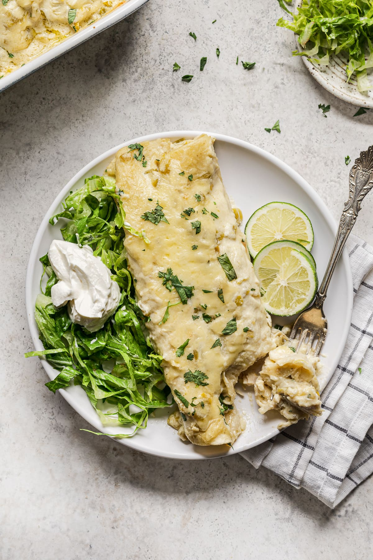 White Chicken Enchilada on a plate with shredded lettuce and sour cream.