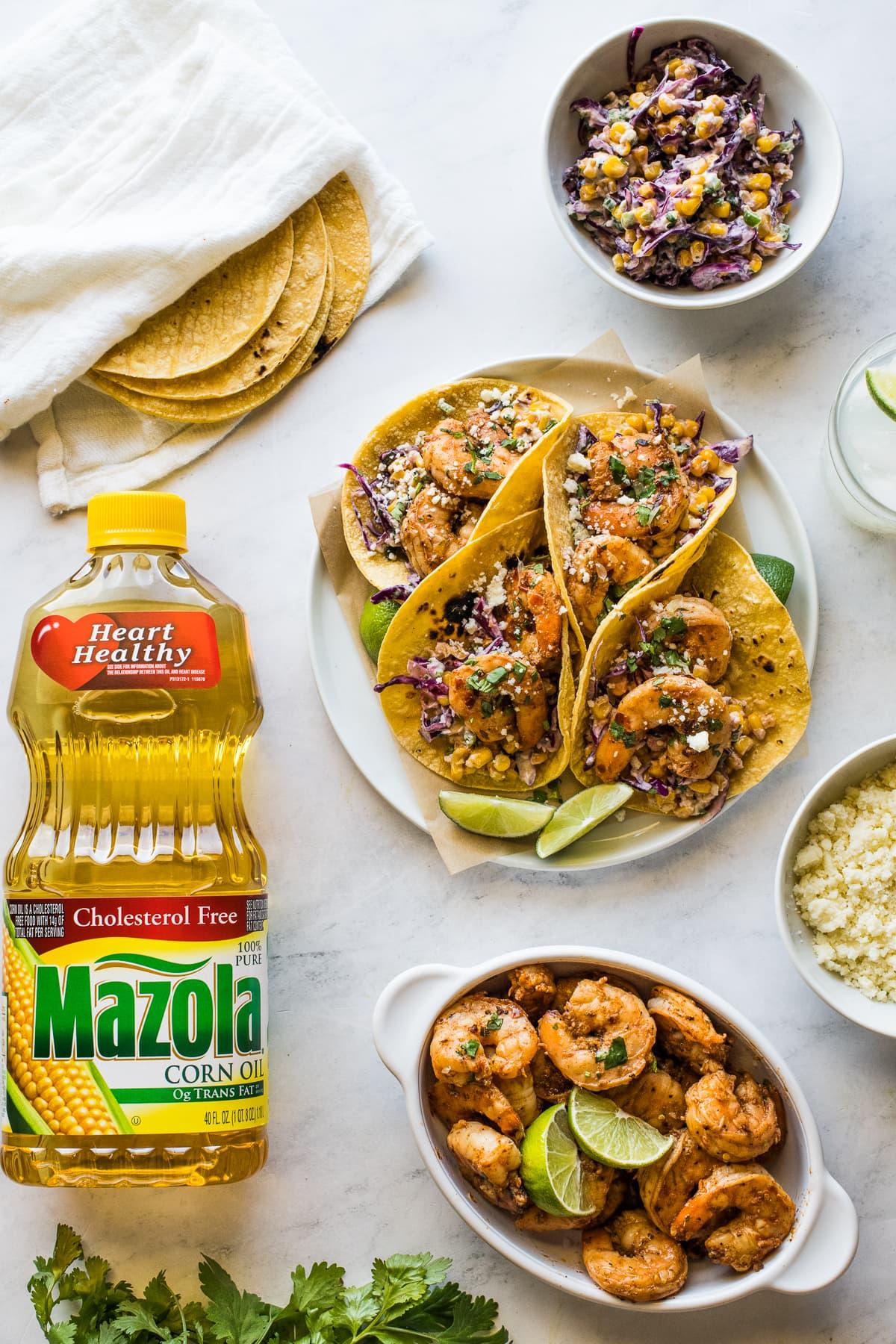 Tacos picantes de camarones en un plato junto a tortillas de maíz, ensalada de elote, queso cotija y más.
